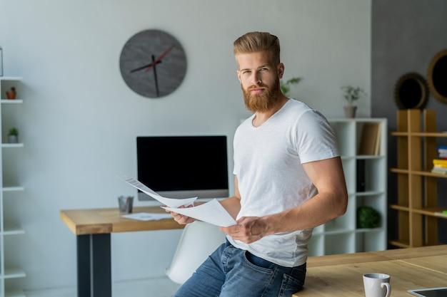 Bärtiger junger geschäftsmann, der am modernen büro arbeitet. mann, der weißes t-shirt trägt und notizen auf den dokumenten macht.