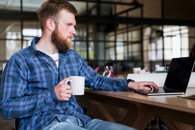 Bärtiger junger geschäftsmann, der an laptop mit dem halten der kaffeetasse arbeitet