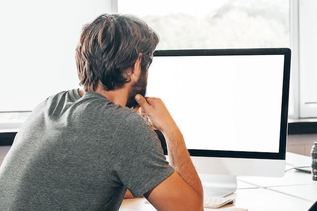 Bärtiger junger geschäftsmann, der im modernen büro arbeitet