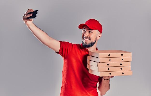 Bärtiger junger liefermann in einem roten t-shirt und einer mütze mit pizzakartons macht ein selfie auf einem smartphone, das auf grauem hintergrund isoliert ist. schnelle lieferung nach hause.