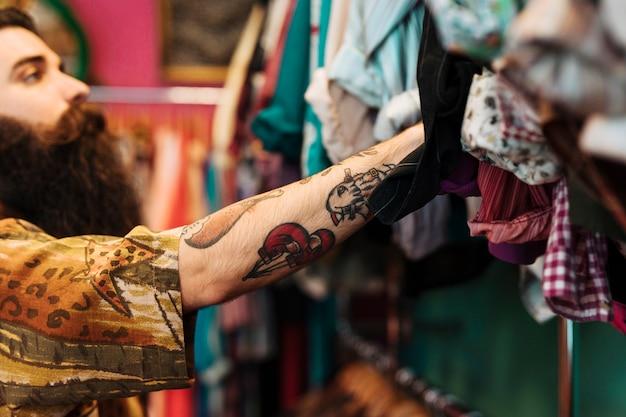 Bärtiger junger mann am hemd, das an der schiene innerhalb des kleidungsshops hängt