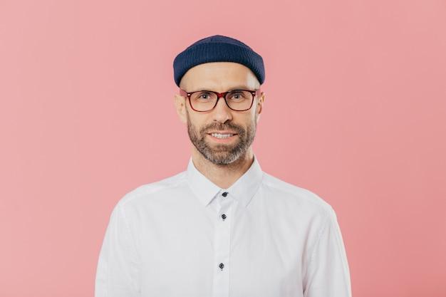 Bärtiger junger mann betrachtet sicher kamera durch schauspiele, trägt weißes formelles hemd
