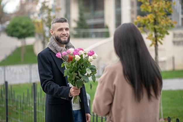 Bärtiger junger mann, der blumen hält, während er für ein date kommt