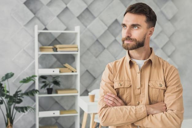 Bärtiger junger mann, der in einem büromittelschuß steht