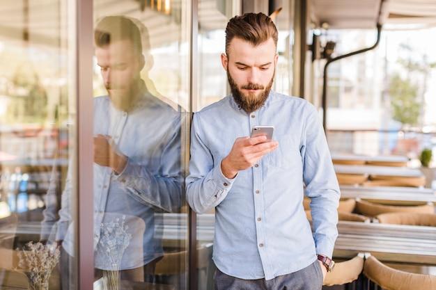 Bärtiger junger mann, der mobiltelefon im caf� verwendet