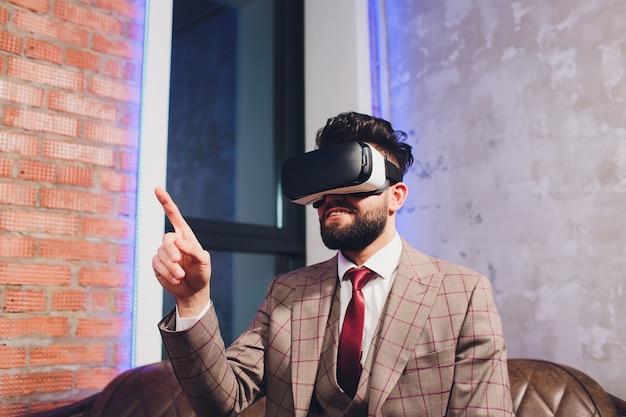 Bärtiger junger mann, der schutzbrille der virtuellen realität im modernen coworking studio trägt.