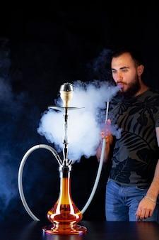 Bärtiger junger mann, der shisha in einem dunklen nachtclub nahaufnahme raucht