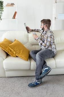 Bärtiger junger mann, der tablette auf dem sofa durchsucht