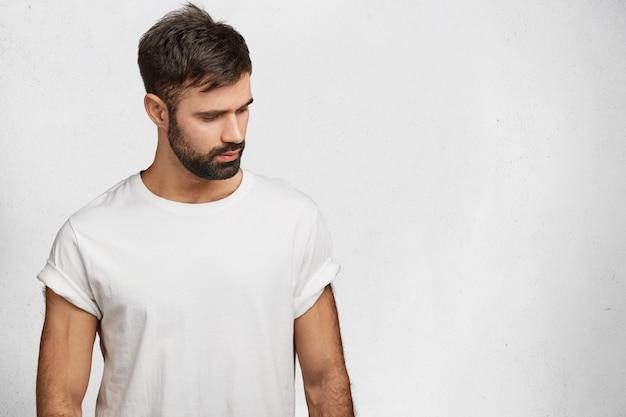 Bärtiger junger mann, der weißes t-shirt trägt