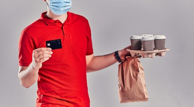 Bärtiger junger mann in rotem t-shirt und mütze in maske hält paket mit fastfood und kaffee einzeln auf grauem hintergrund. zahlung per kreditkarte. schnelle lieferung vom restaurant zu ihnen nach hause.