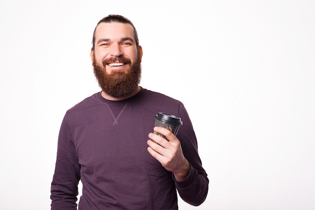 Bärtiger junger mann lächelt in die kamera und hält eine tasse mit heißem getränk