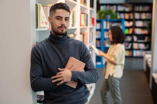 Bärtiger junger mann mit buch, das gegen weibliche literatur steht