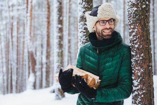 Bärtiger junger mann trägt warmen hut und grüne jacke