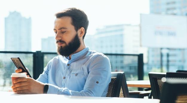 Bärtiger kaukasischer mann, der mit jemandem auf der terrasse während einer kaffeepause plaudert