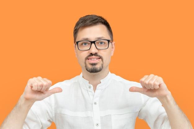 Bärtiger kaukasischer mann mit brille, der sich mit den fingern anzeigt. gut aussehender kerl, der selbstbewusst mit einem lächeln im gesicht aussieht und sich stolz und glücklich isoliert auf gelbem hintergrund zeigt.