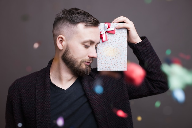 Bärtiger kaukasischer mann mit einem geschenk auf seiner schulter posiert in formeller kleidung auf einer grauen studiowand mit konfetti