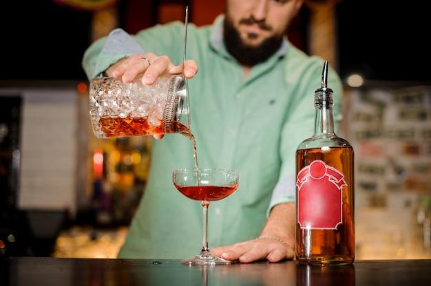 Bärtiger kellner, der ein alkoholisches getränk in ein glas gießt