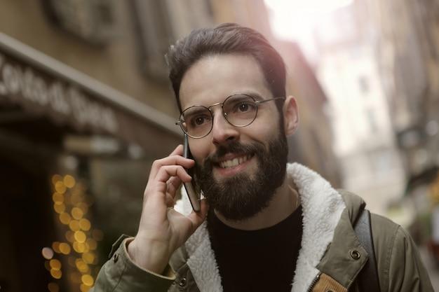 Bärtiger kerl, der auf einem smartphone spricht