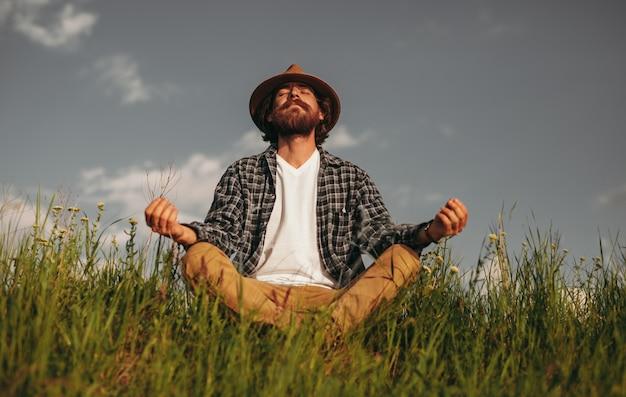 Bärtiger kerl, der im feld meditiert, während er in lotushaltung sitzt