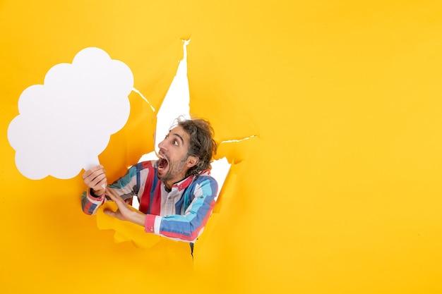 Bärtiger kerl, der weißes wolkenförmiges papier hält und angst vor etwas in einem zerrissenen loch und freiem hintergrund in gelbem papier hat