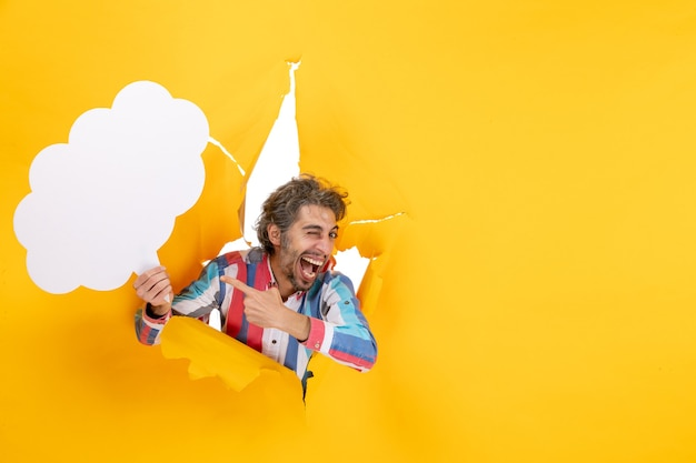 Bärtiger kerl, der weißes wolkenförmiges papier hält und etwas mit glücklichem gesichtsausdruck in ein zerrissenes loch und freien hintergrund in gelbem papier zeigt