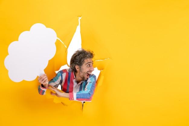 Bärtiger kerl, der weißes wolkenförmiges papier hält und etwas mit überraschtem gesichtsausdruck in einem zerrissenen loch und freiem hintergrund in gelbem papier betrachtet