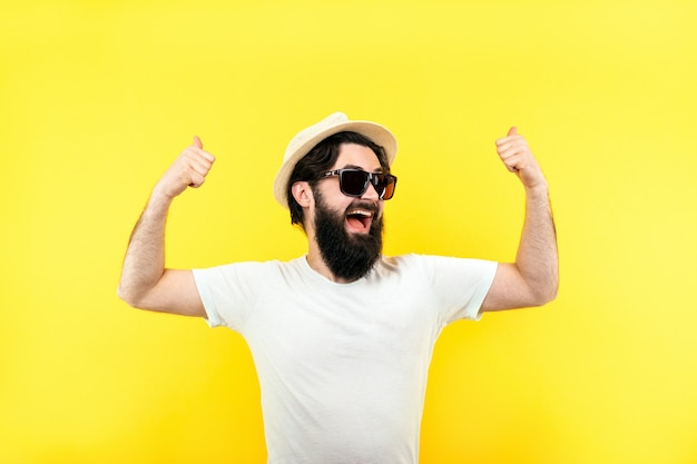 Bärtiger kerl in sonnenbrille und panamahut, mann zeigt wie auf gelbem hintergrund