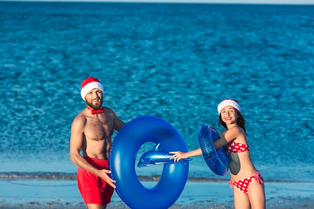 Bärtiger kerl und mädchen in weihnachtsmützen spielen mit aufblasbaren kreisen und einem aufblasbaren delphin am meeresstrand.