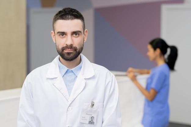 Bärtiger kliniker im weißen kittel, der sie im stehen ansieht