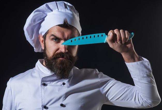 Bärtiger koch mit messer. ernster koch mit blauem messer in der hand werbung für restaurants. kochen.