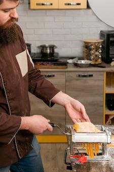 Bärtiger koch mit nudelmaschine macht gelben teig für nudeln