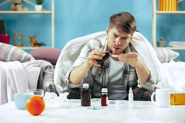 Bärtiger kranker mann mit kamin, der auf sofa zu hause bedeckt bedeckt ist