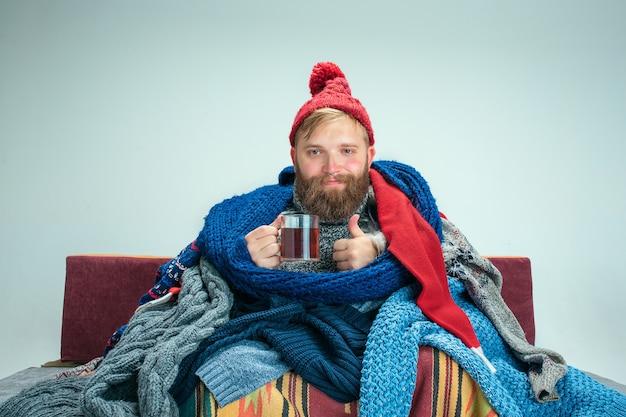 Bärtiger kranker mann mit kamin, der auf sofa zu hause oder im studio mit tasse tee sitzt, der mit gestrickter warmer kleidung bedeckt ist. krankheit, influenza-konzept. entspannung zu hause. gesundheitskonzepte.