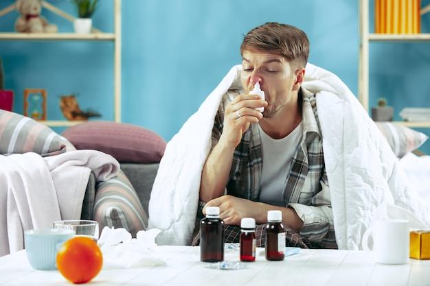 Bärtiger kranker mann mit kamin, der zu hause auf sofa sitzt, mit warmer decke bedeckt und nasenspray verwendet. das krankheits-, influenza-, schmerzkonzept. entspannung zu hause