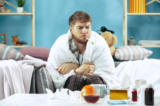 Bärtiger kranker mann mit kamin, der zu hause auf sofa sitzt und körpertemperatur misst. der winter, krankheit, influenza, schmerzkonzept. entspannung zu hause. gesundheitskonzepte.