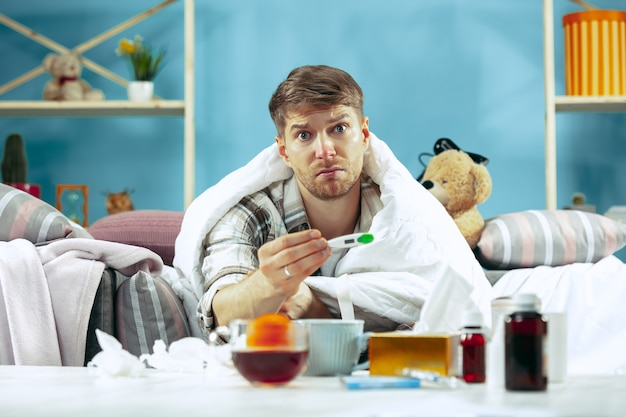 Bärtiger kranker mann mit kamin, der zu hause auf sofa sitzt und körpertemperatur misst. der winter, krankheit, influenza, schmerzkonzept. entspannung zu hause