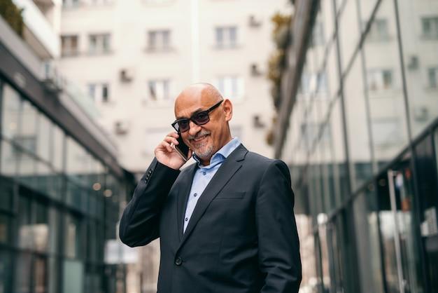 Bärtiger lächelnder älterer erwachsener, der smartphone für geschäftsgespräche beim stehen auf der straße verwendet.