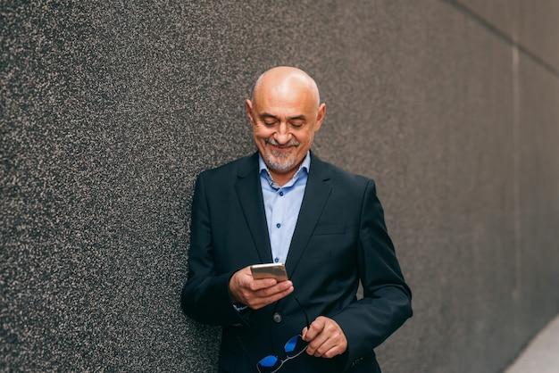 Bärtiger lächelnder älterer erwachsener, der smartphone verwendet, während er sich an die wand lehnt und in der anderen hand brille hält.