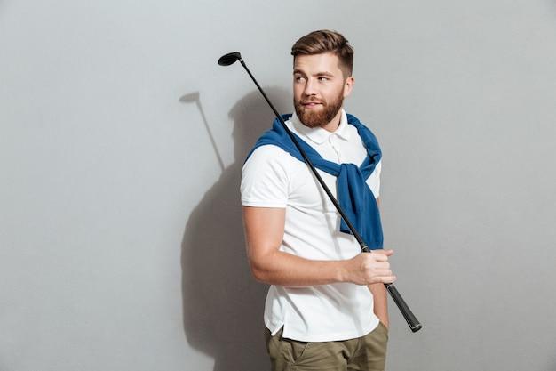 Bärtiger lächelnder golfer, der mit verein in der hand aufwirft