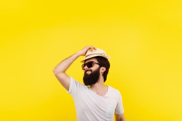 Bärtiger lächelnder mann in panama über gelbem hintergrund