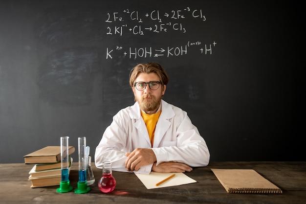 Bärtiger lehrer der chemie, der röhre mit rosa flüssiger substanz beim sitzen am tisch vor smartphone-kamera bei lektion betrachtet