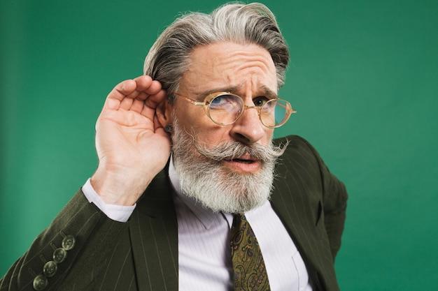 Bärtiger lehrer mittleren alters im anzug hält ohr und lauscht auf grüner wand