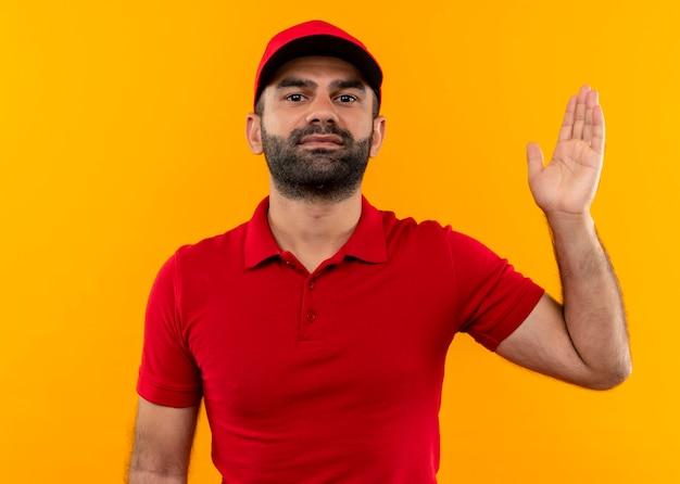 Bärtiger lieferbote in der roten uniform und im arm der kappe, die zuversichtlich schauen, über orange wand stehend