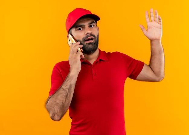 Bärtiger lieferbote in der roten uniform und in der kappe, die auf handy sprechen, der verwirrt und sehr ängstlich steht und über orange wand steht