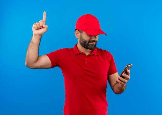Bärtiger lieferbote in der roten uniform und in der kappe, die bildschirm seines handys betrachten zeigefinger, der zuversichtlich steht, über blauer wand stehend