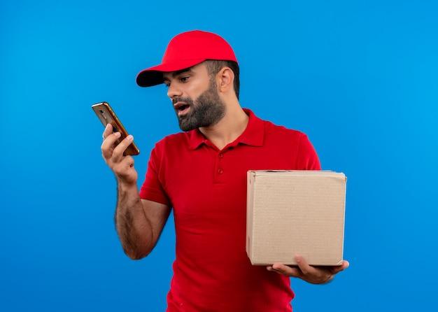 Bärtiger lieferbote in der roten uniform und in der kappe, die box-paketaufzeichnungs-sprachnachricht unter verwendung seines smartphones hält, das über blaue wand steht