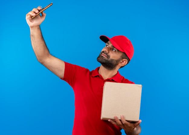 Bärtiger lieferbote in der roten uniform und in der kappe, die box-verpackungs-selfie mit seinem smartphone hält, das über blauer wand steht