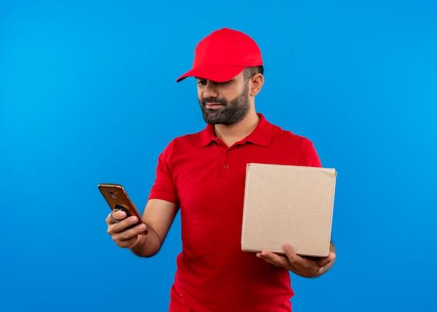Bärtiger lieferbote in der roten uniform und in der kappe, die boxpaket hält, das bildschirm seines handys mit ernstem gesicht betrachtet, das über blauer wand steht