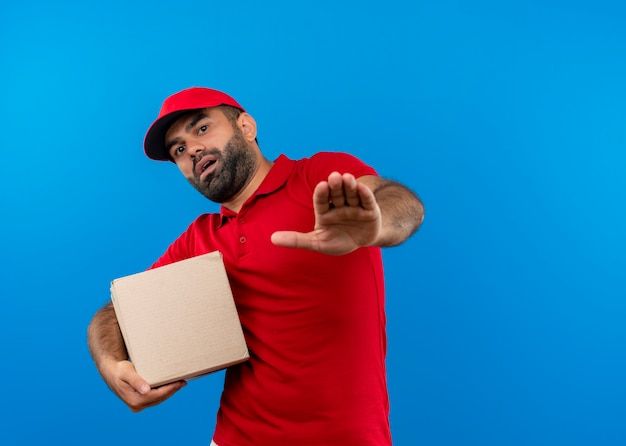Bärtiger lieferbote in der roten uniform und in der kappe, die boxpaket hält, das stoppschild mit furchtausdruck macht, der über blauer wand steht