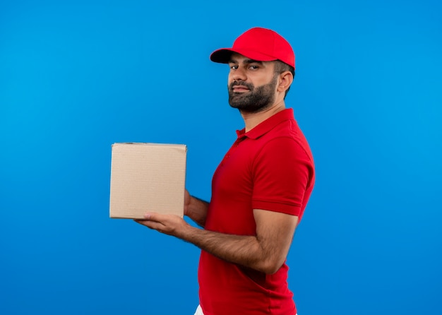 Bärtiger lieferbote in der roten uniform und in der kappe, die boxpaket hält, das zuversichtlich steht, seitlich über blauer wand zu stehen